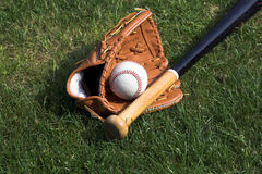 Baseball. Bat and glove against a grass background royalty free stock photography