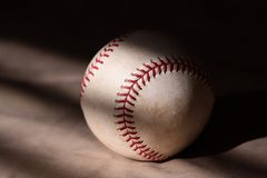 Baseball. A major league baseball against a brown backdrop in morning light Royalty Free Stock Image