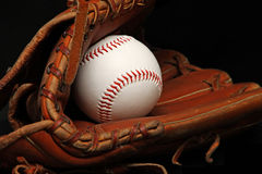 Baseball. Clean, new baseball inside a leather catcher's glove in black background