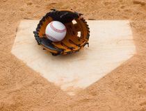 Baseball. And glove set on home plate Royalty Free Stock Photos