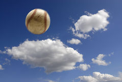 Baseball in air. Baseball flying through the air with clouds and sky in background Royalty Free Stock Photo