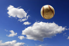 Baseball in air. Baseball flying through the air with clouds and sky in background Royalty Free Stock Photography