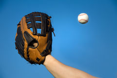 Baseball in air about to be caught by glove. Baseball in air about to be caught by glove with blue sky background. Room for adding your own copy space Royalty Free Stock Photos