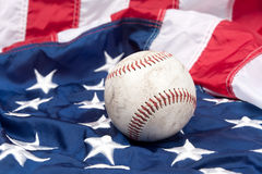Baseball on American flag. A scuffed up baseball on an American flag Royalty Free Stock Images