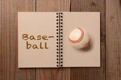 Baseball auf offenem Notizbuch Stockbild