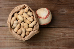 Baseball and a Bag of Peanuts. A bag of peanuts and a baseball on an old wooden bench at the ballpark. Horizontal format with copy space Royalty Free Stock Photo