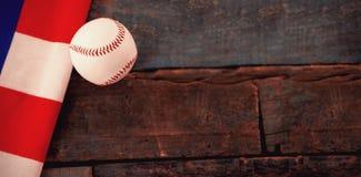 Baseball ball and American flag on table