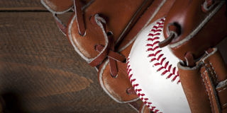 Baseball ball, glove and bat on wooden table Stock Images