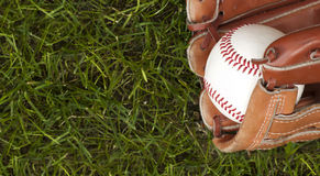 Baseball ball and glove on green grass Stock Images