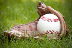 Baseball ball and glove on green grass Royalty Free Stock Photo