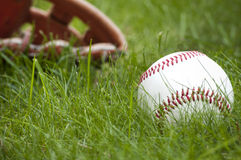 Baseball ball and glove on green grass Stock Photography