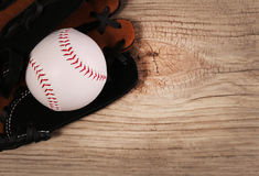 Baseball. Ball in Glove over wood background Stock Photo
