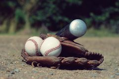 Baseball ball in leather glove with a baseball bat lying on the playground Stock Photography