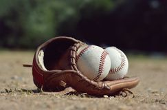 Baseball ball in leather glove lying on the playground Royalty Free Stock Image