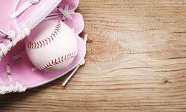 Baseball. Ball in Pink Female Glove over wood background Stock Photo