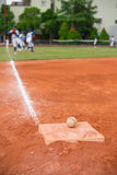 Baseball and base on baseball field with players practising Stock Image