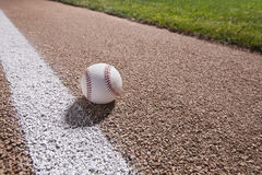Baseball on a base path under lights at night. A baseball sits on a base path near the stripe under the lights at night royalty free stock image