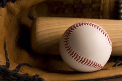 Baseball and baseball bat in glove Stock Images