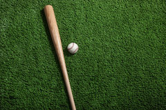 Baseball bat and ball on green turf background. A wooden baseball bat and baseball on a green turf background viewed from above stock photo