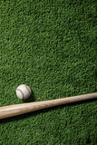 Baseball bat and ball on green turf background. A wooden baseball bat and baseball on a green turf background viewed from above Royalty Free Stock Photo
