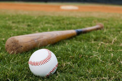 Baseball and Bat on Field. Baseball and old bat on field with base and outfield in background Royalty Free Stock Photography