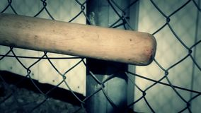 Baseball bat with focus on wire fence