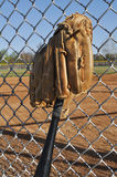 Baseball Bat and Glove. Leaning Against the Backstop Stock Photography
