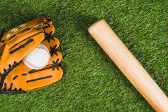 Baseball bat with glove and ball on green grass. Top view of baseball bat with glove and ball on green grass Royalty Free Stock Images