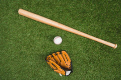 Baseball bat with glove and ball on green grass. Top view of baseball bat with glove and ball on green grass Stock Photo
