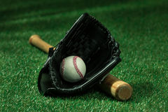 Baseball bat, glove and ball lying on green field royalty free stock photo