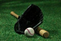 Baseball bat, glove and ball lying on green grass. Closeup view of baseball bat, glove and ball lying on green grass Royalty Free Stock Image