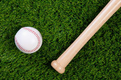 Baseball and bat on grass. Photo of a baseball and wooden bat on grass Stock Photography