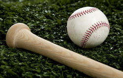 A baseball and Bat on Green Grass Royalty Free Stock Photo