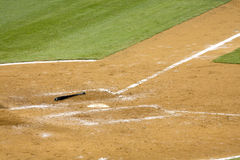 Baseball bat on ground. Baseball bat laying on ground near home plate Stock Photo