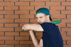 Baseball bat. Guy in dark blue tshirt holds bright green bat. Ready to hit. Man in green cap on red brick wall background. Sports and baseball training concept Stock Image