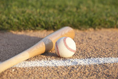 Baseball and bat laying on basepath with grass infield Stock Image