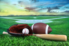 Baseball, bat, and mitt in field at sunset Stock Photo