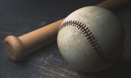 Baseball and bat on wooden surface. Close up of baseball and bat on aged wooden surface. 3D Rendering Royalty Free Stock Photography