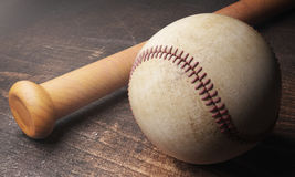 Baseball and bat on wooden table. Close up of baseball and bat on aged wooden table. 3D Rendering Stock Photography