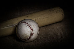Baseball and Bat. A worn baseball and bat sit atop a burlap surface. Image was lit by using a lightpainting technique stock photography