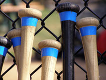 Baseball Bats. Leaning against a batting cage fence Stock Image