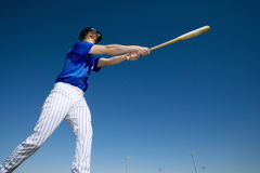 Baseball batter, in blue uniform, hitting ball during competitive game, side view, low angle view (tilt) Royalty Free Stock Photo