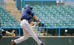 Baseball batter swinging at ball - ball in frame Stock Image