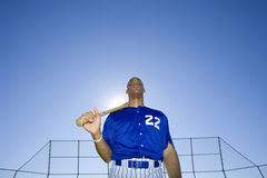 Baseball batter, wearing number �22� blue uniform, standing on pitch with bat resting on shoulder, front view, portrait, low a Royalty Free Stock Images