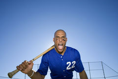 Baseball batter, wearing number �22� blue uniform, standing on pitch with bat resting on shoulder, shouting, front view, portr Stock Photography