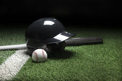 Baseball batting helmet bat and ball on field with stripe and da. A baseball batting helmet bat and ball on a field with a white stripe and dark background Royalty Free Stock Photos