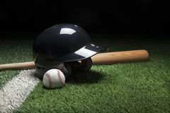 Baseball batting helmet bat and ball on field with stripe Royalty Free Stock Image