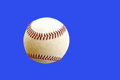 Baseball on blue background. Close up of a new official baseball isolated on a medium blue background, making it look as if it is suspended in mid-air on a clear Stock Image