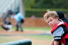 Baseball catcher leaning over dugout fence looking at camera. Stock Photos