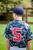 Baseball boy outside from behind in camo jersey Royalty Free Stock Photo